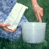 Photo of woman scooping soil into a soil sample test kit